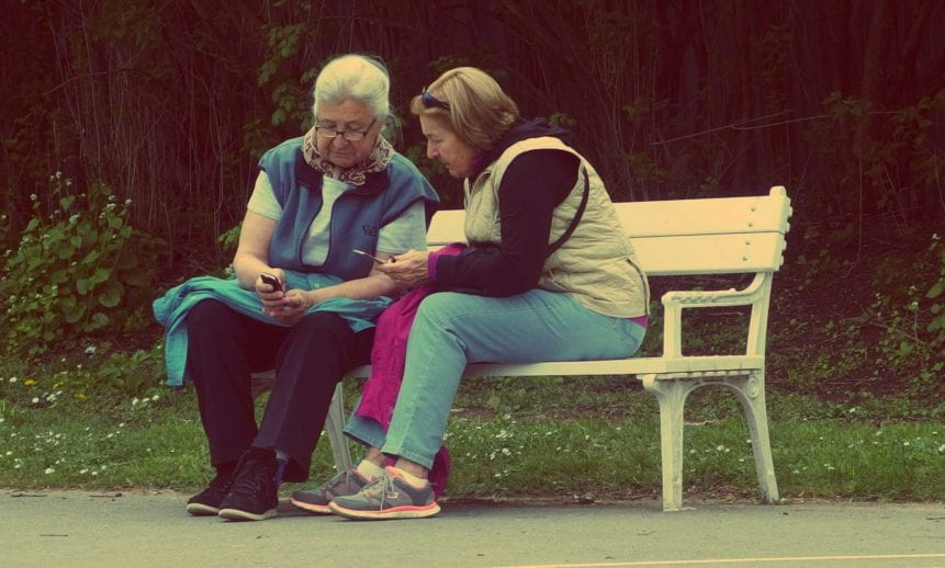 elderly person and a middle aged person talking on a park bench